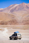 Lonely car going trough Salvador Dali Desert in Altiplano, Bolivia — Stock Photo