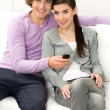 Young couple with TV remote — Stock Photo #28188631
