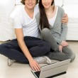 Stock Photo: Young couple using laptop at home