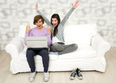Young couple using laptop on couch — Stock Photo
