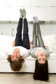 Couple upside down on sofa laughing — Stock Photo