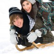 Young couple on sled in snow — Stock Photo #28195353