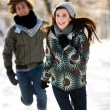 Couple running in the snow — Stock Photo #28195467