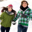 Couple running in the snow — Stock Photo #28195541