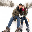 Young couple on sled in snow — Stock Photo #28195661