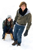 Man pulling woman on sled — Stock Photo