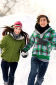Couple running in the snow — Stock Photo