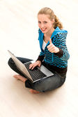 Happy woman with thumbs up using laptop — Stock Photo