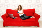 Woman sitting on couch with laptop — Stock Photo