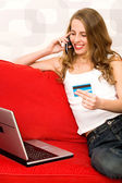 Woman using laptop, holding credit card — Stock Photo