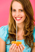 Woman holding orange with straw — Stock Photo