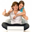 Couple using laptop showing thumbs up — Stock Photo