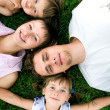 Family lying on grass — 图库照片