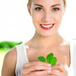 Woman holding green leaves — Stock Photo