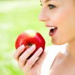 Woman holding an apple in her hand — Stock Photo