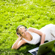 Stock Photo: Womwith headphones and laptop outdoors