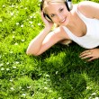 Young woman laying on grass listening to music — Stock Photo