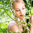 Woman touching flowers on tree — Stock Photo