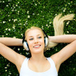 Stock Photo: Woman lying on grass with headphones