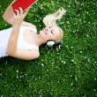 Woman lying on grass with book and headphones — Стоковая фотография