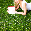 Woman lying on grass, reading book — Stock Photo