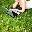 Woman laying on grass using laptop — ストック写真