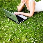 žena na trávě pomocí přenosného počítače — Stock fotografie