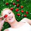 Young woman lying on grass with strawberries — Stock Photo
