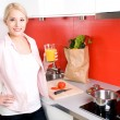 Stock Photo: Young woman standing in kitchen