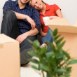 Couple on floor next to moving boxes — Stock Photo
