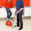 Man vacuuming, woman in background — Stock Photo #28263699