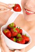 Woman eating strawberries — Stock Photo