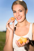 Young woman holding apricots — Stock Photo