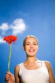 Woman holding flower against blue sky — Stock Photo