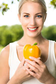 Woman holding yellow pepper — Stock Photo