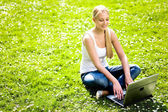 Young woman sitting on grass using laptop — Stock Photo