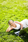 Woman with headphones and laptop outdoors — Stock Photo