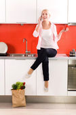 Woman sitting on kitchen counter — Stock Photo