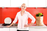 Young woman standing in kitchen — Stock Photo