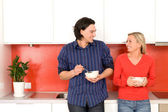 Couple in kitchen holding bowls — Stock Photo