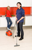 Man vacuuming, woman in background — Stock Photo