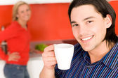 Couple in kitchen, man holding coffee cup — Stock Photo
