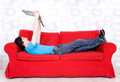 Young man lying on couch with laptop — Stock Photo