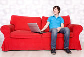 Man sitting on couch with laptop — Stock Photo