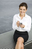 Businesswoman using palmtop outdoors — Stock Photo
