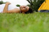 Uomo disteso sull'erba vicino tenda — Foto Stock