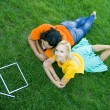Couple lying on the grass with model house in front of them — Stock Photo #28272393