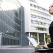 Businesswoman using laptop outside office — Stock Photo