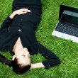 Businesswoman sleeping beside a laptop — Stock Photo