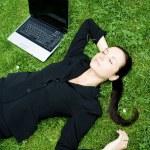 Businesswoman sleeping beside a laptop — Stock Photo #28270113